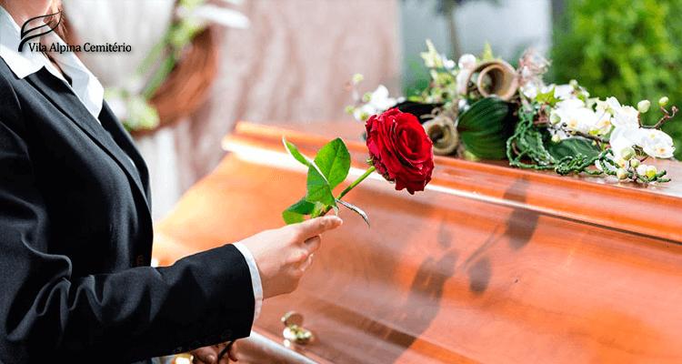 mulher segurando uma rosa perto de um caixão no funeral