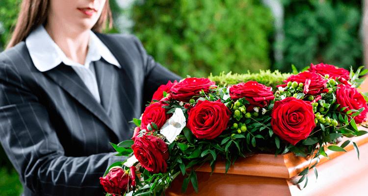 mulher ao lado de um caixão coberto de rosas em um funeral