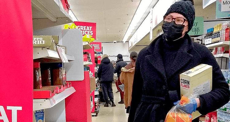 Mulher de máscara fazendo compras no mercado - coronavírus