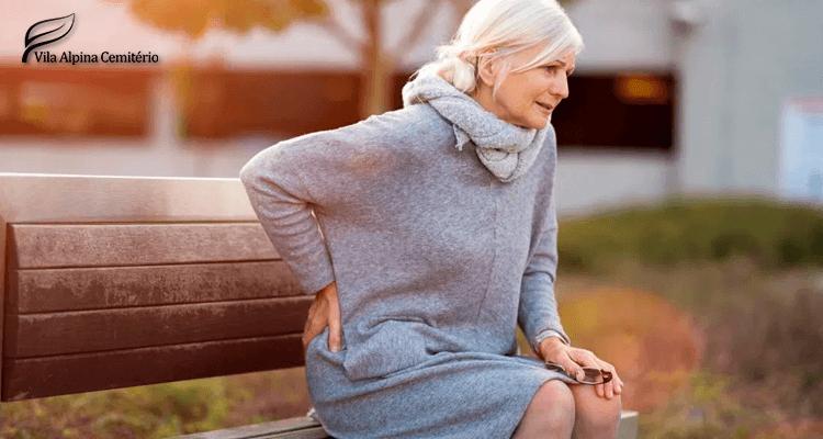 Mulher sentada em banco com dor nas costas - osteoporose